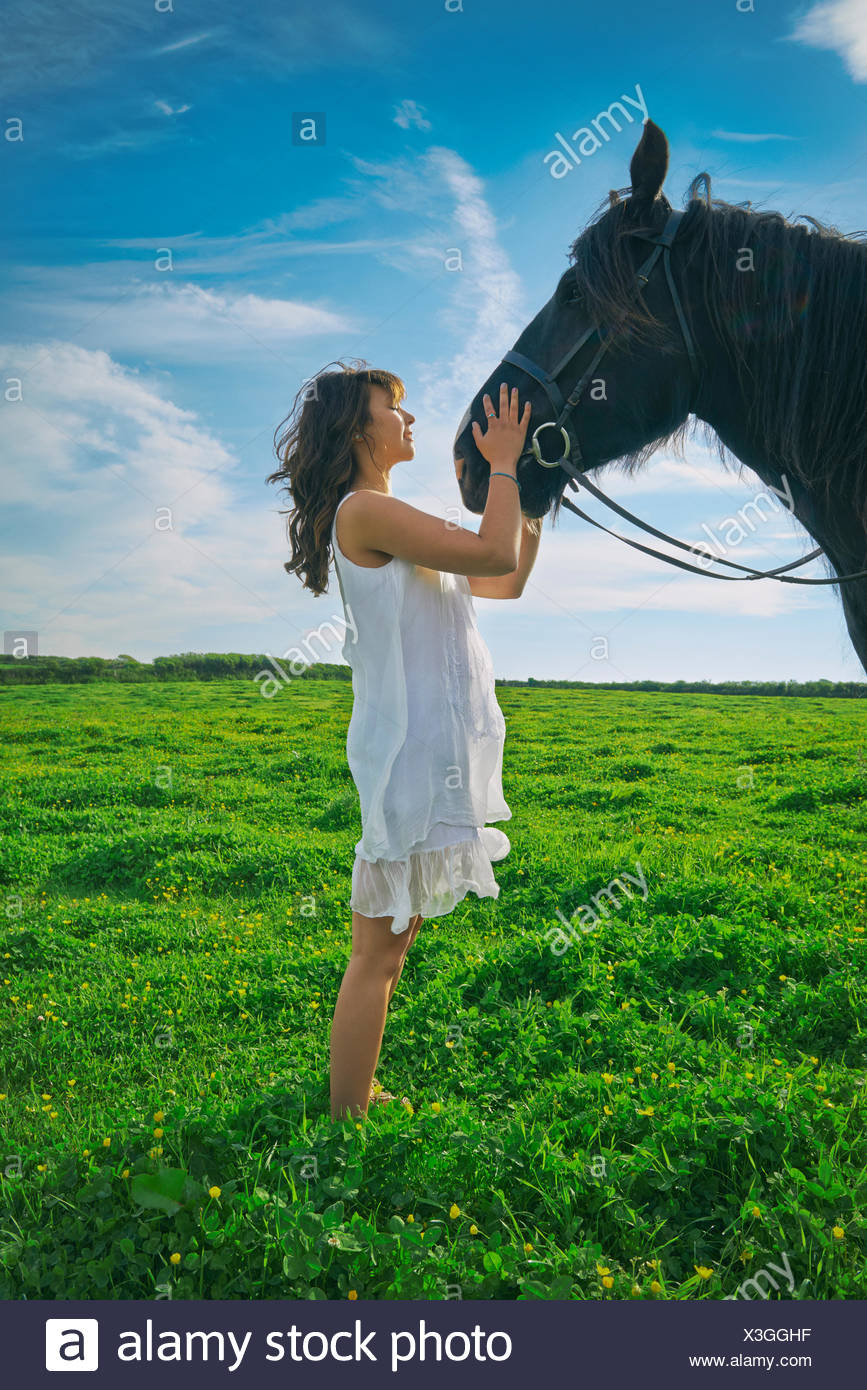 Young woman petting horse in field - Stock Image