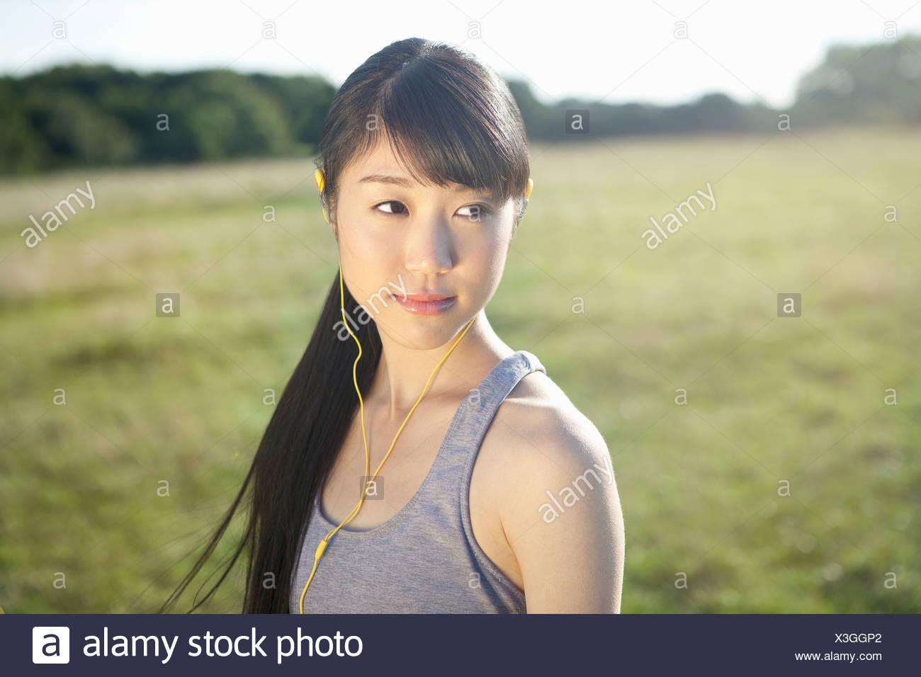 Portrait of young female runner wearing earphones Stock Photo
