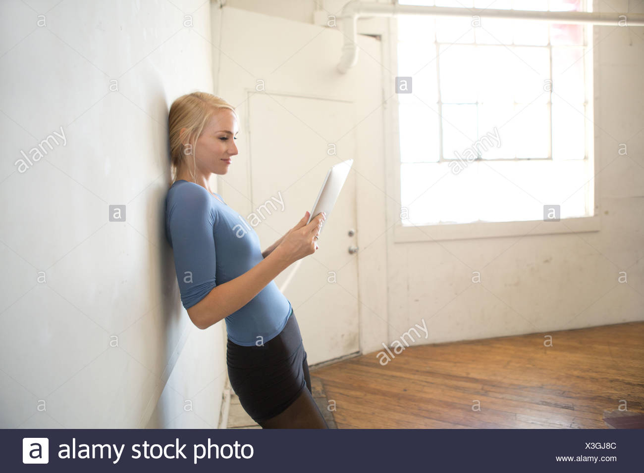 Female dancer leaning against wall using digital tablet Stock Photo
