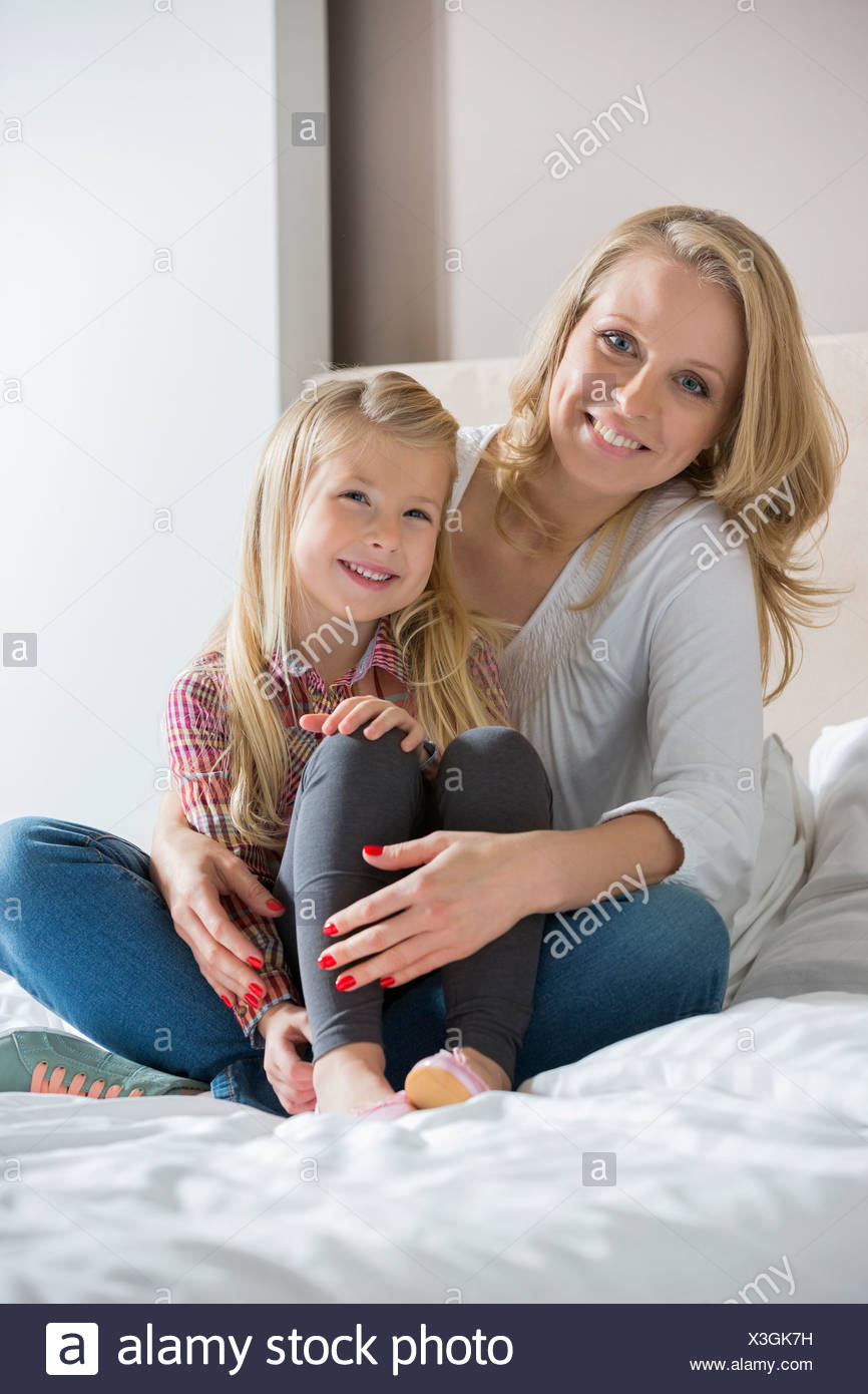 Portrait of happy mother and daughter sitting on bed at home Stock Photo
