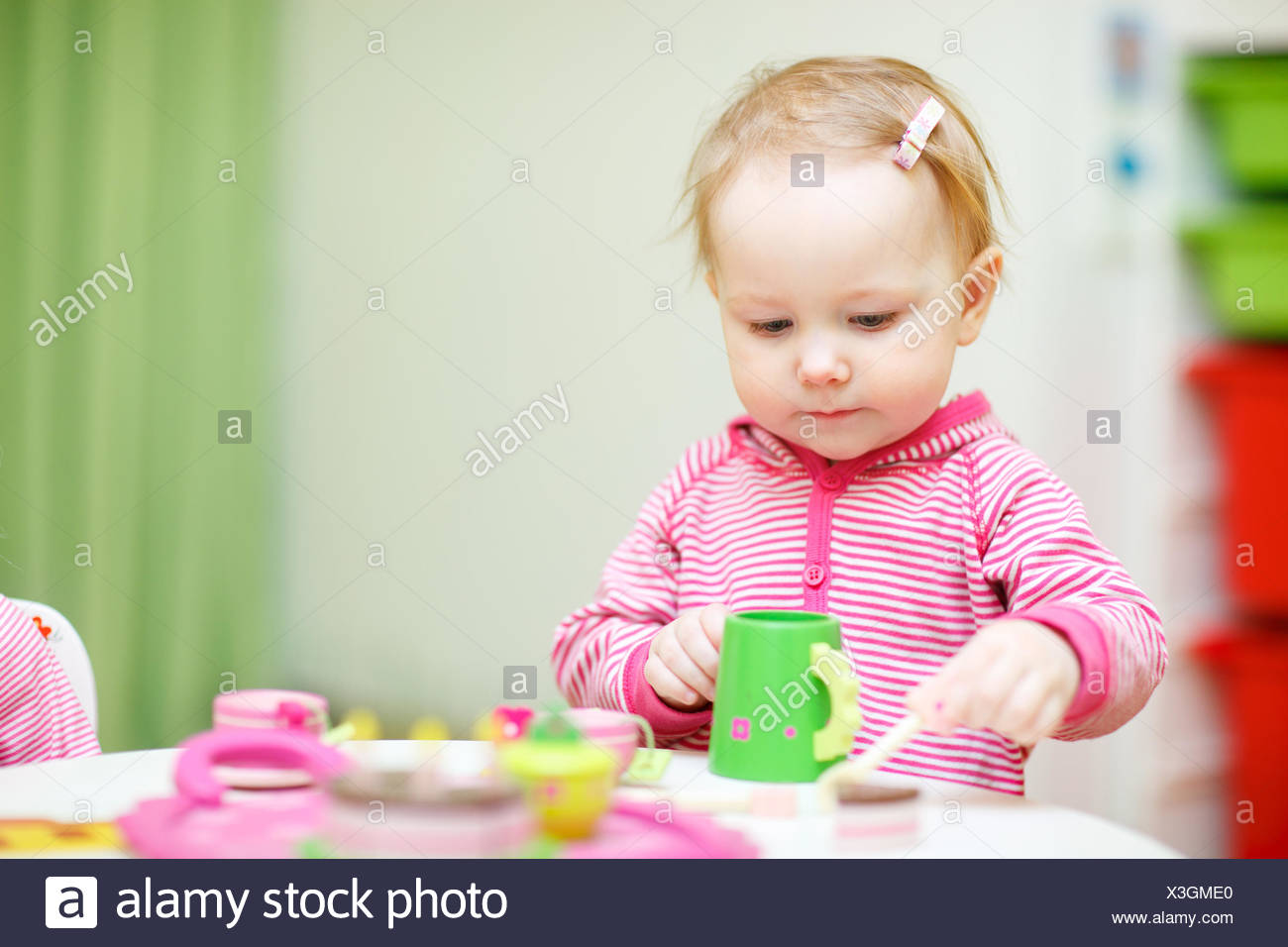 little girl plays drink coffee with plastic toys - Stock Image