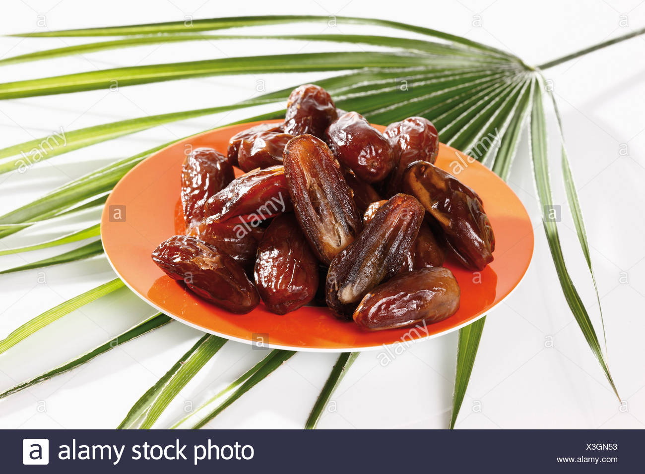 Dried Dates on plate, elevated view - Stock Image