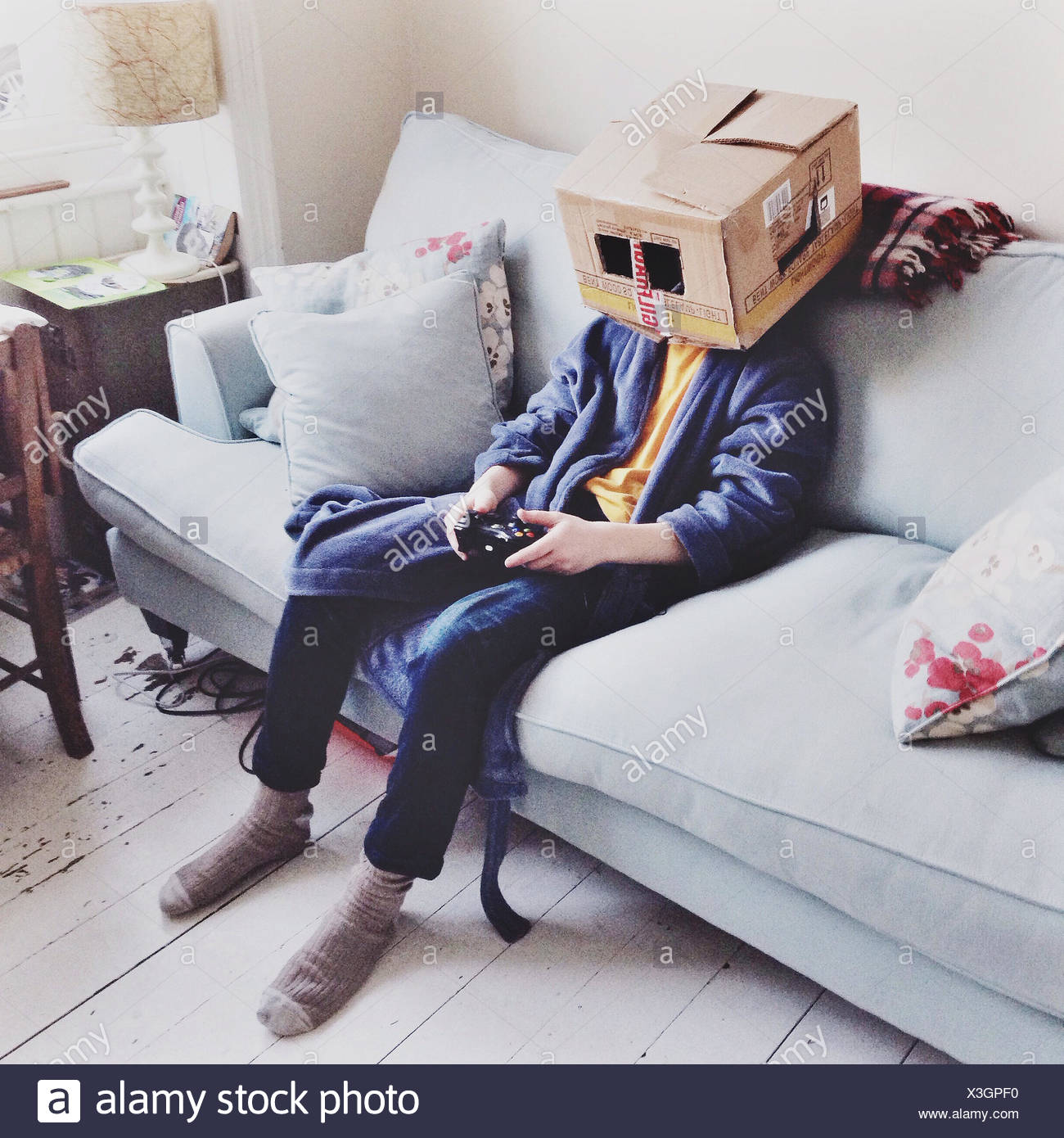 United Kingdom, England, Brighton, Box Head (12-13) watching television - Stock Image