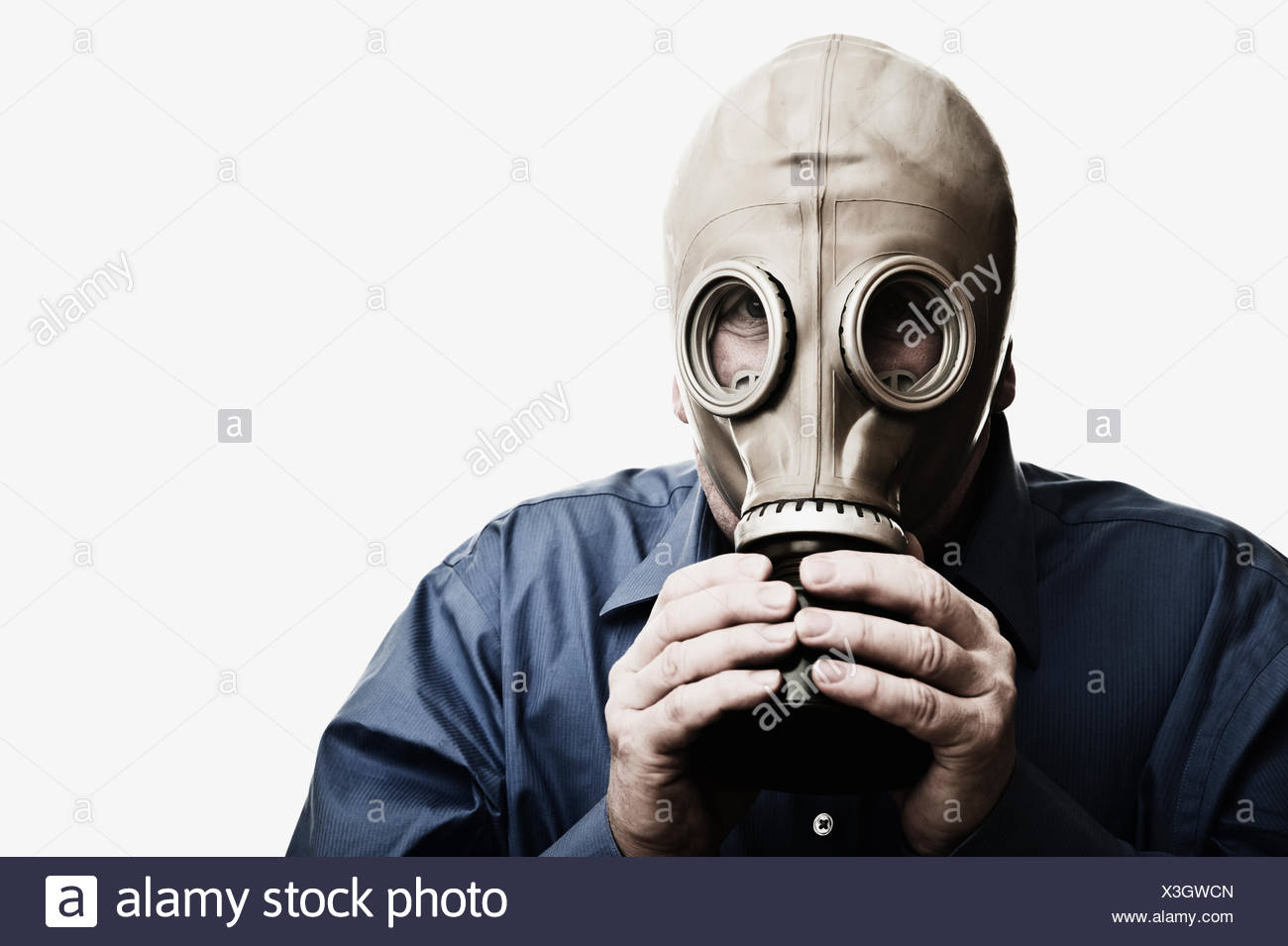Studio shot of man trying to breath in gas mask - Stock Image