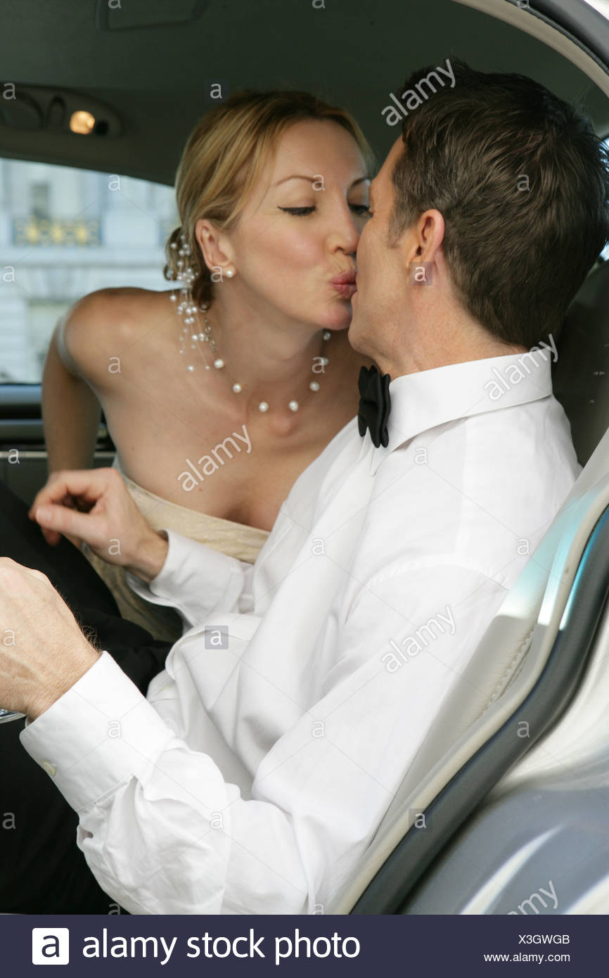 mature couple kissing in the backseat of a car stock photo