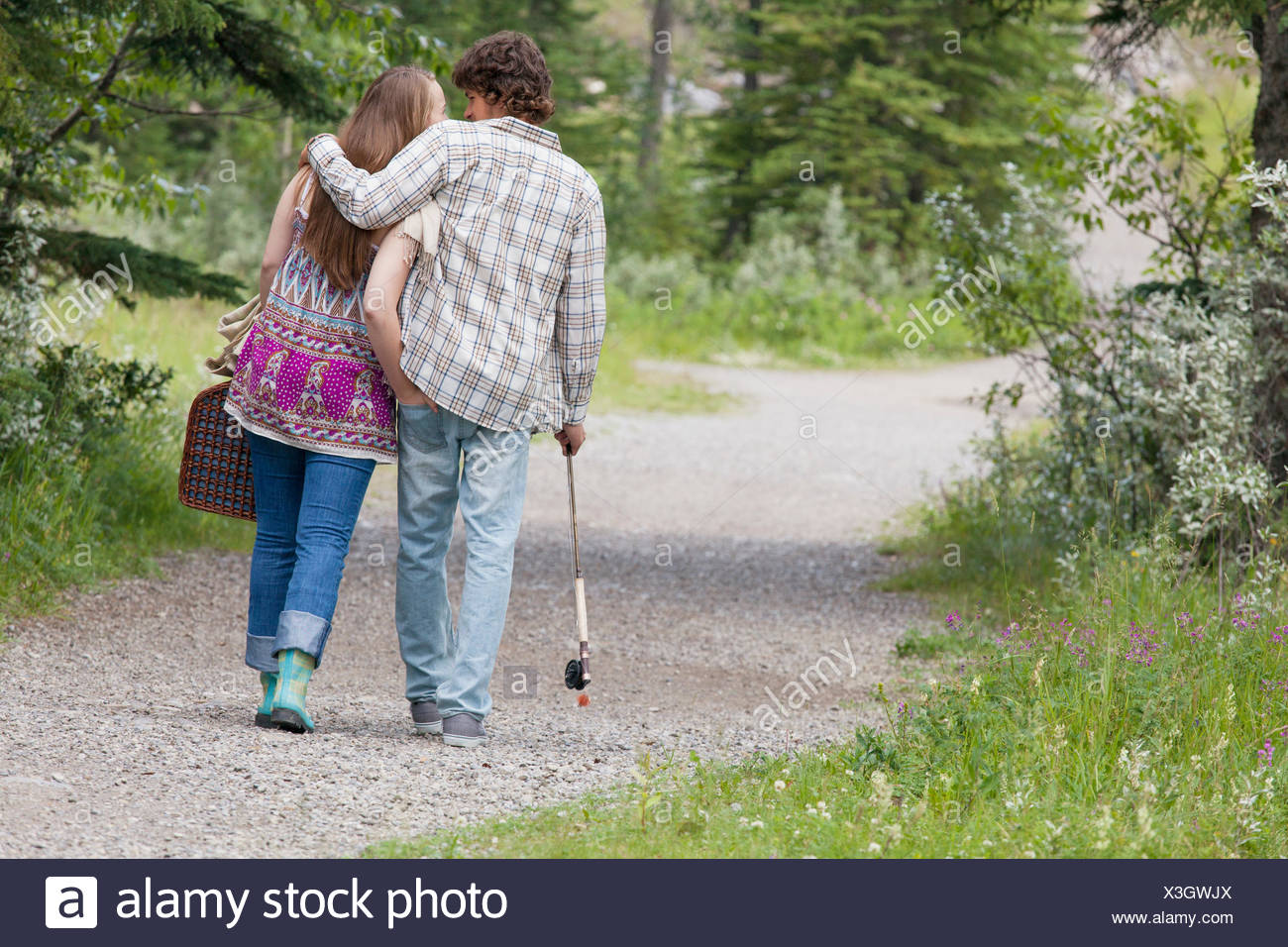 view from behind of young couple walking with picnic basket - Stock Image
