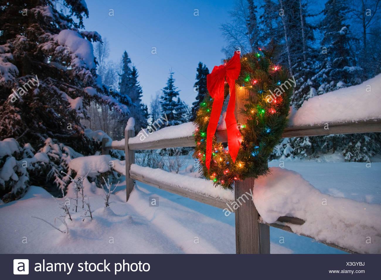 Decorated Christmas wreath hangs on a snowcovered split rail fence at dusk, Alaska Stock Photo