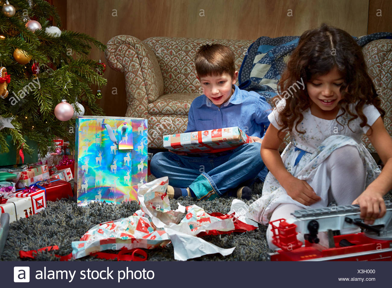 Sister and brother in sitting room unwrapping and playing with christmas gifts Stock Photo