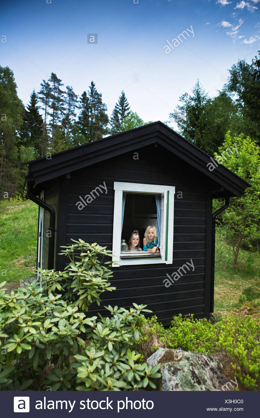 Girls looking out window of shack - Stock Image