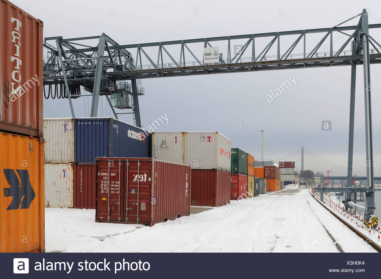 Winter at Bonn Harbour, snow-covered quay, view of container terminal and portainer, North Rhine-Westphalia, Germany, Europe - Stock Image