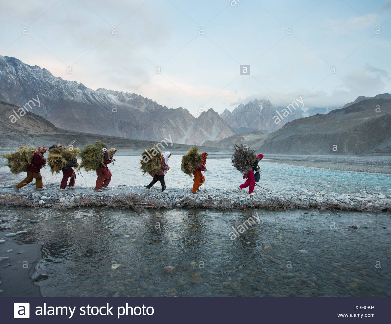 Women returning from getting wood for cooking and heating and hay to feed their livestock, a two hour walk. - Stock Image