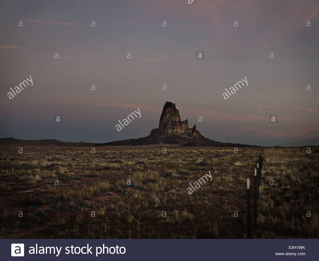 Rock formation in grassy desert - Stock Image