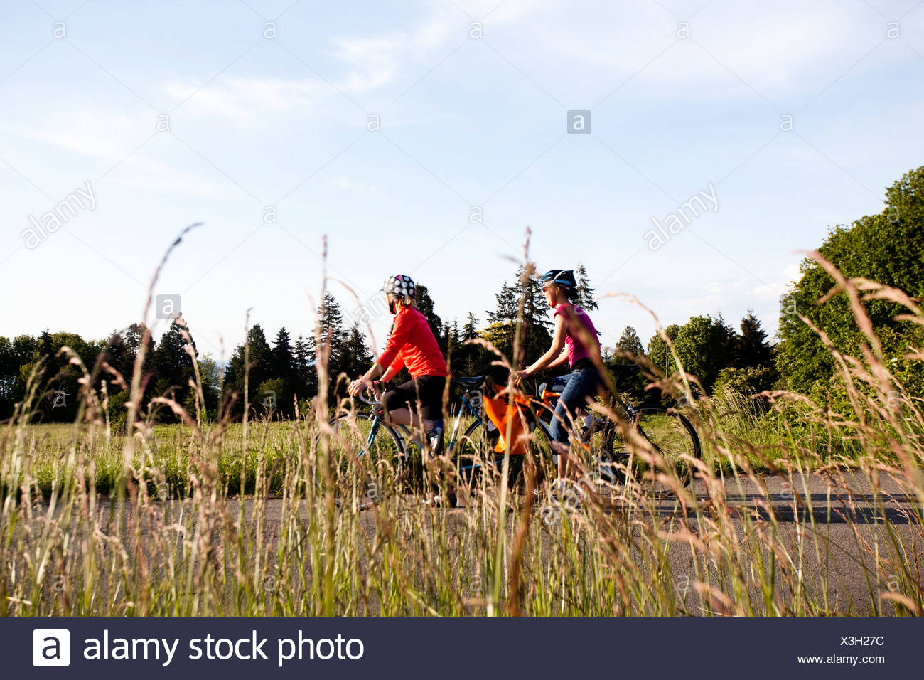 Two young women enjoy ther view on the ride home from work through a park. - Stock Image