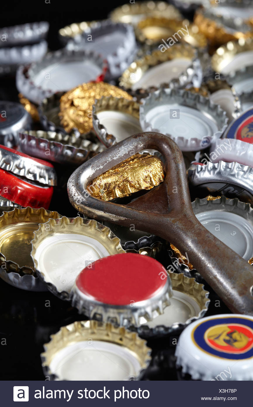 Bottle opener and crown caps, close-up - Stock Image