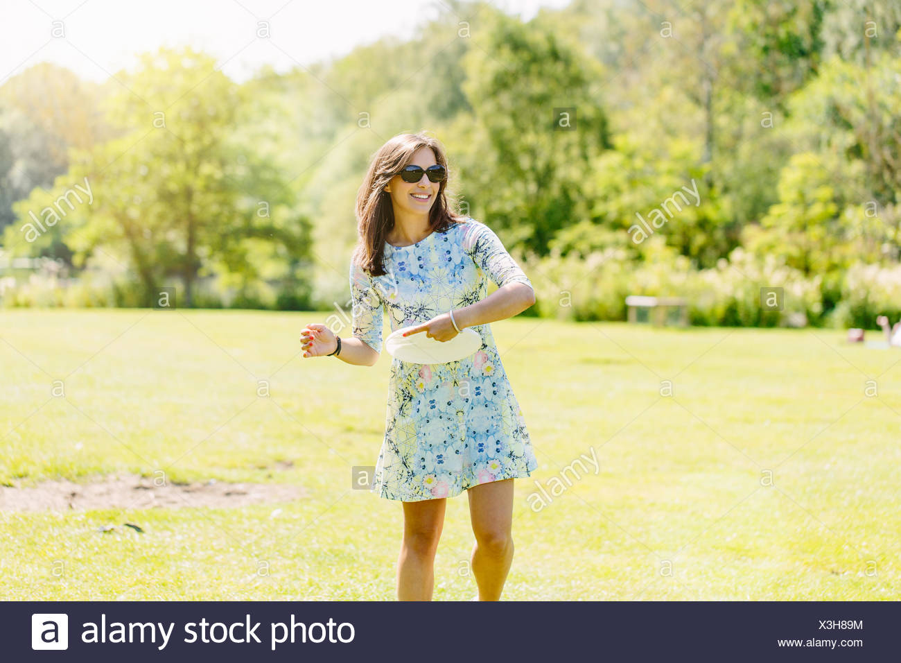 Woman playing disc game in the park - Stock Image