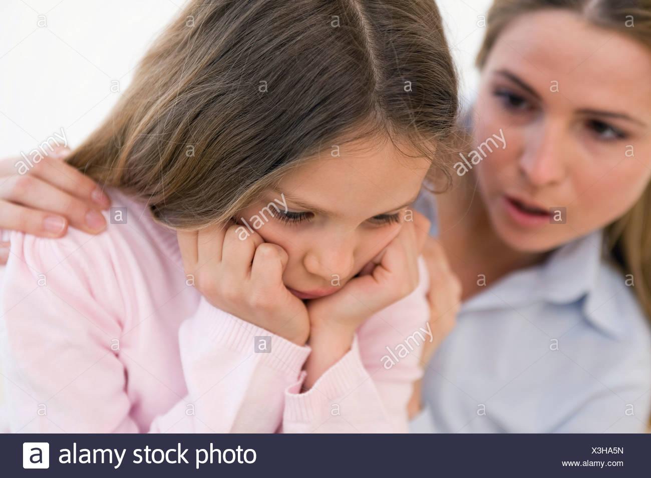 Portrait mother consoling daughter, studio shot - Stock Image