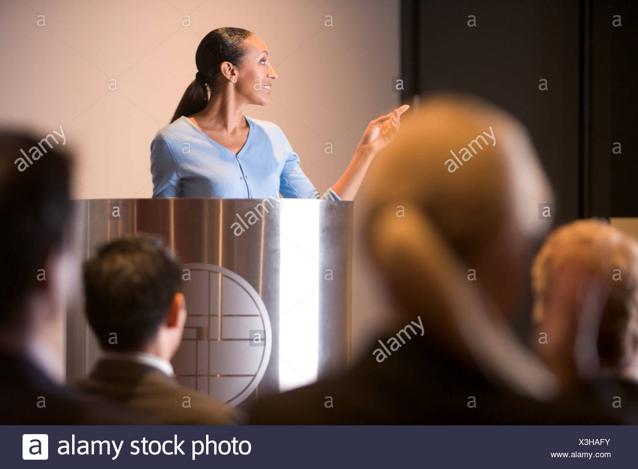 Businesswoman giving presentation at podium - Stock Image