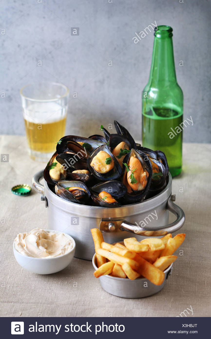 Cooked mussels in an aluminum pan with french fries,mayonnaise and a glass of beer - Stock Image