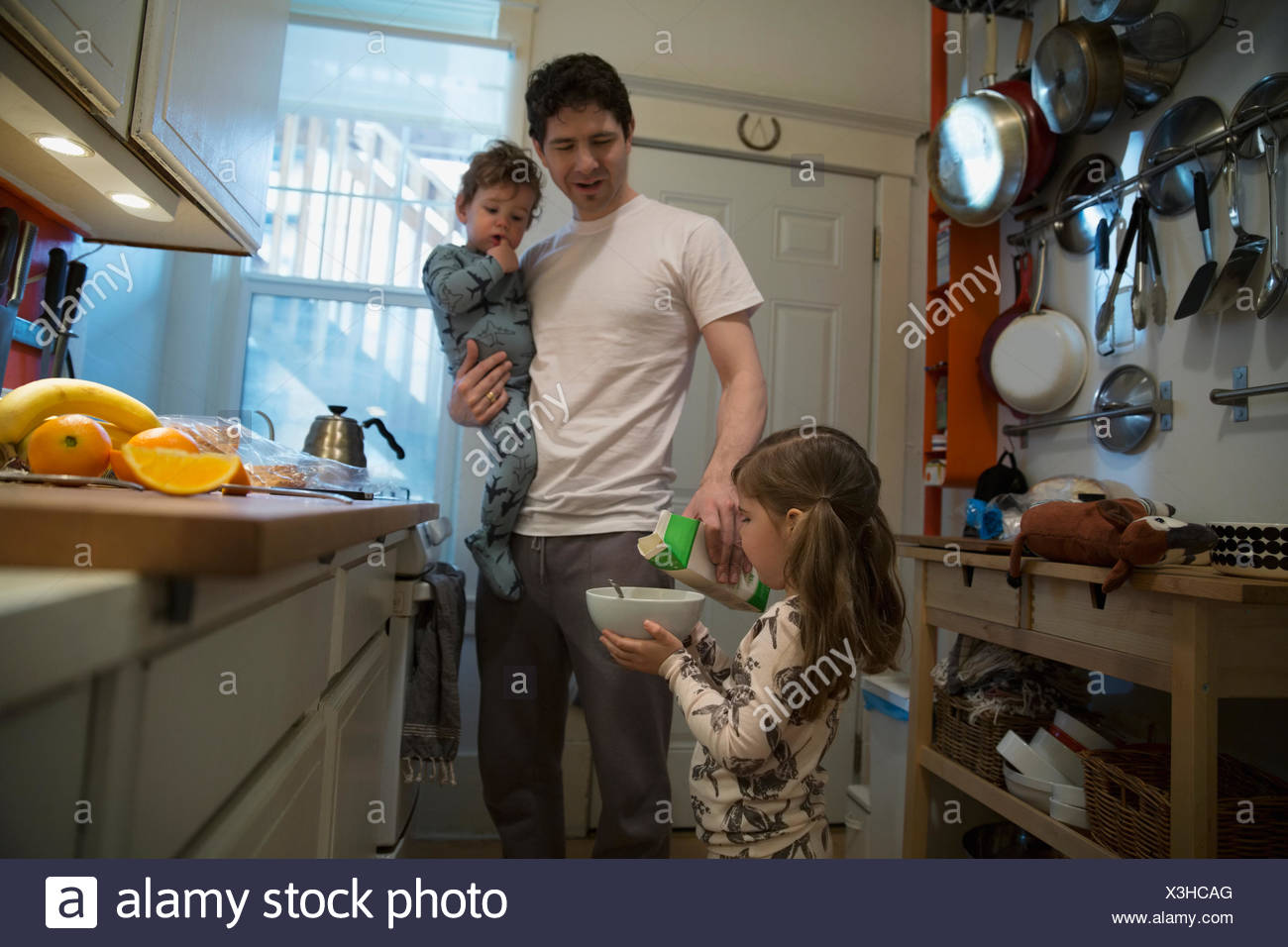 Girl holding bowl of cereal in kitchen - Stock Image