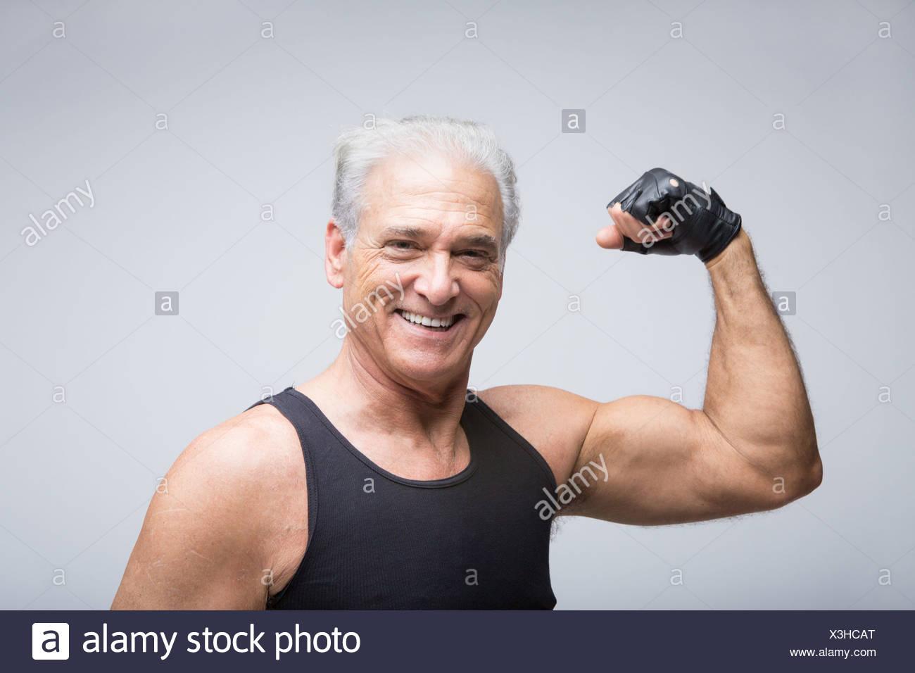 Senior man flexing muscle, portrait - Stock Image