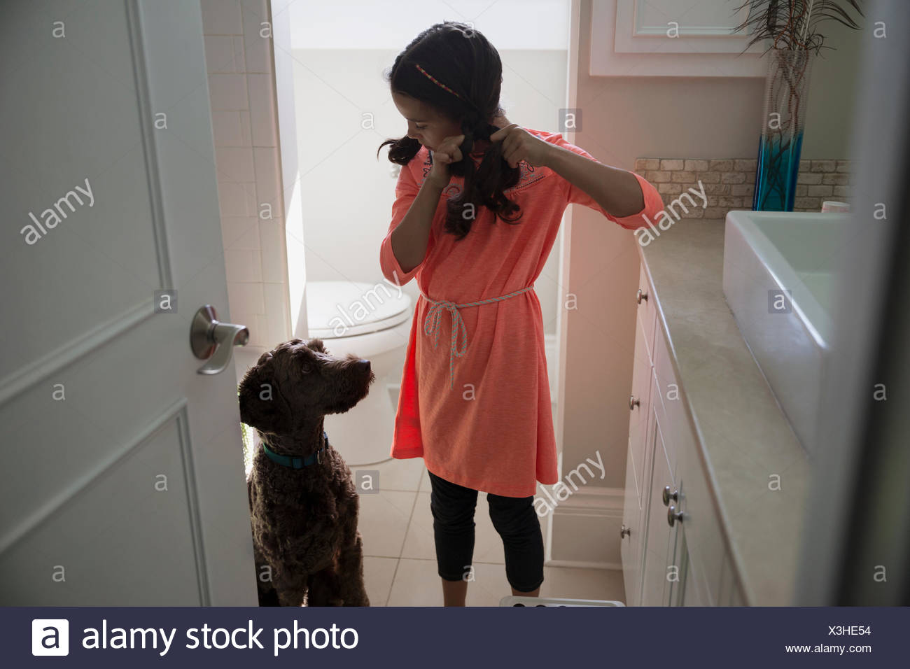 Dog watching girl fix hair in bathroom - Stock Image