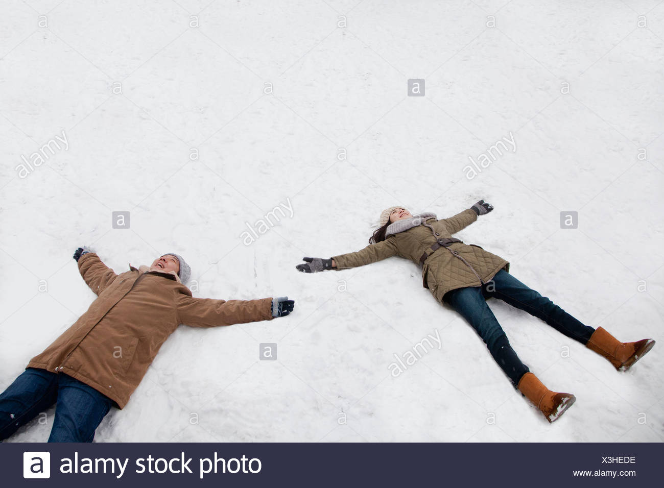 Young couple laying in snow making snow angels - Stock Image