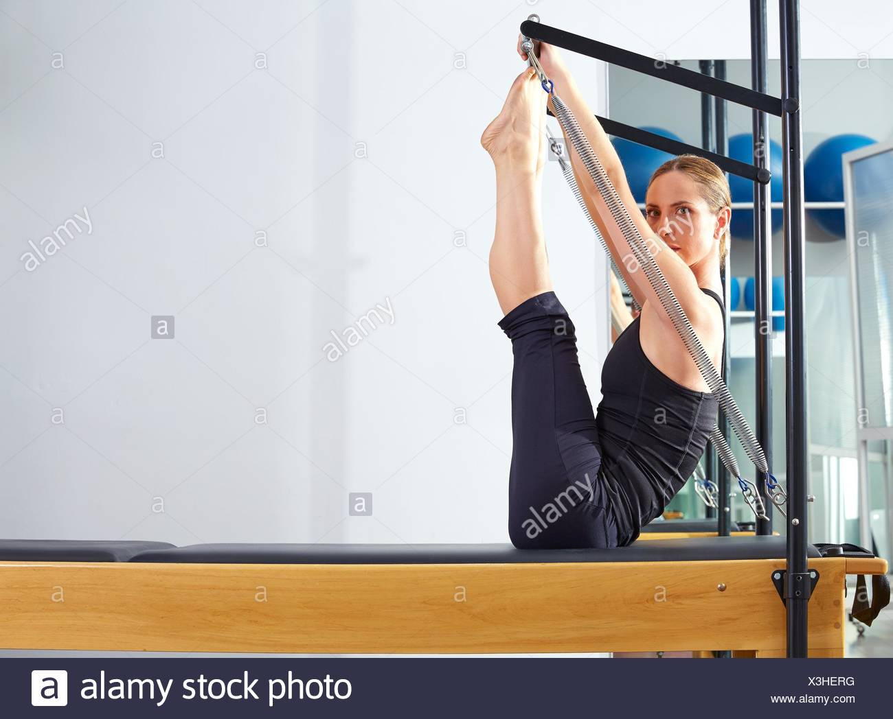 Pilates woman in reformer monki exercise at gym indoor. - Stock Image
