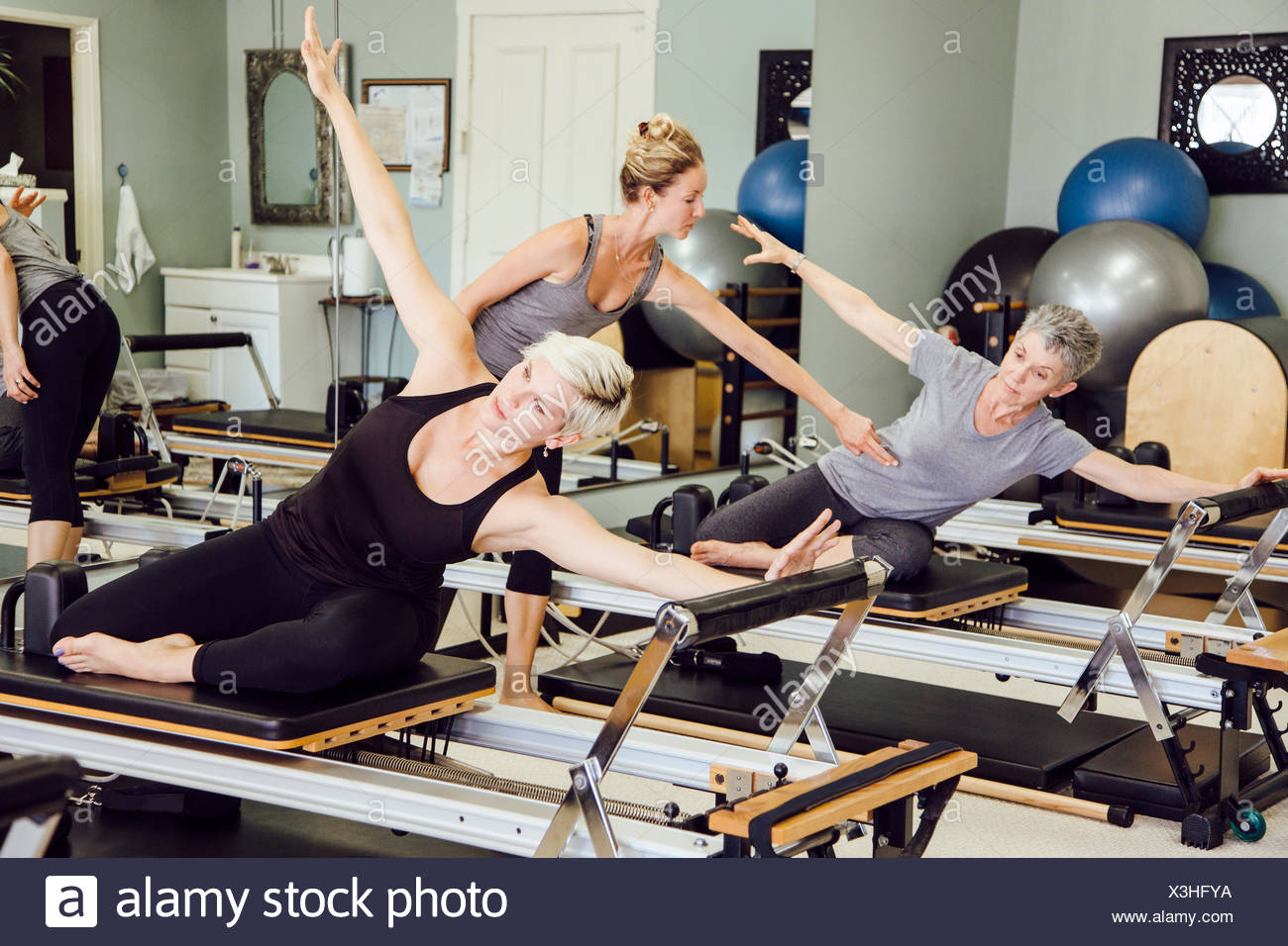 Women in gym using pilates reformer - Stock Image