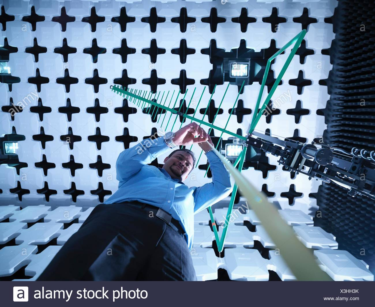 Engineer checking a bilog antenna's height for electromagnetic compatibility (EMC) radiated immunity testing in a semi anechoic chamber, low angle view - Stock Image