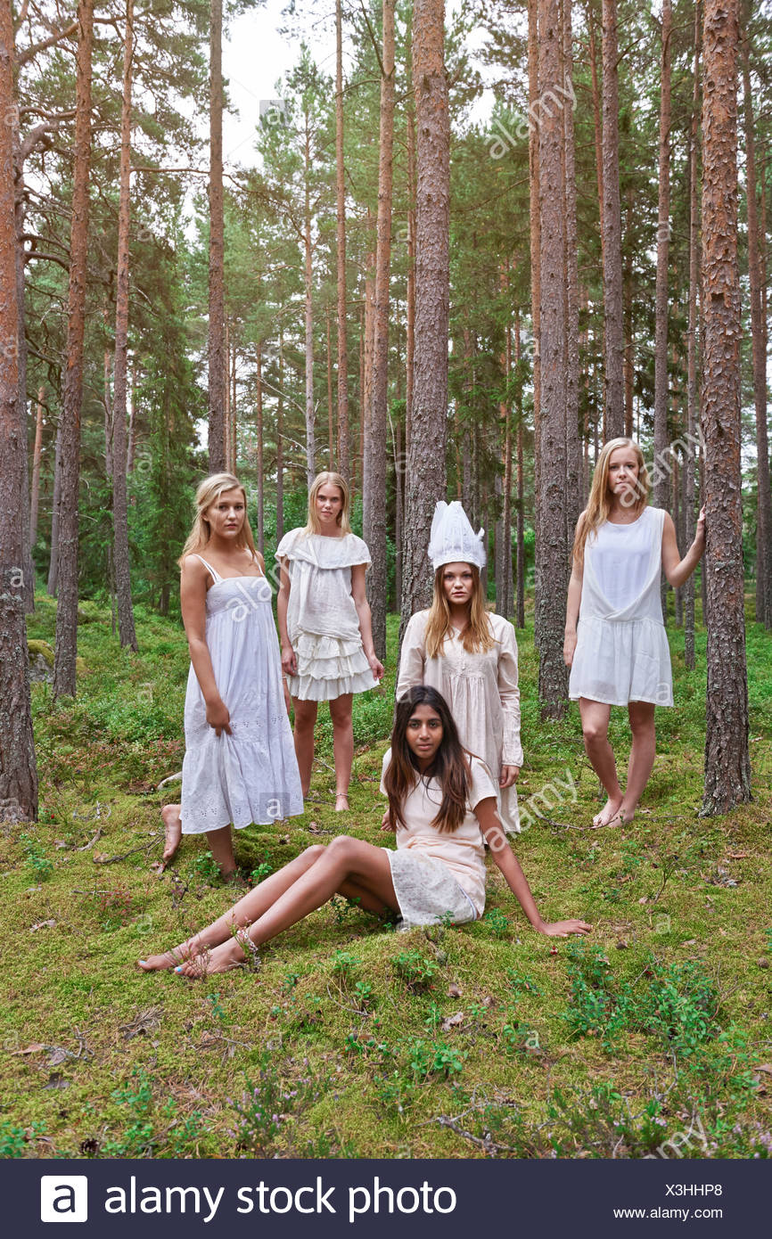 Teenage girls wearing white dresses in forest - Stock Image