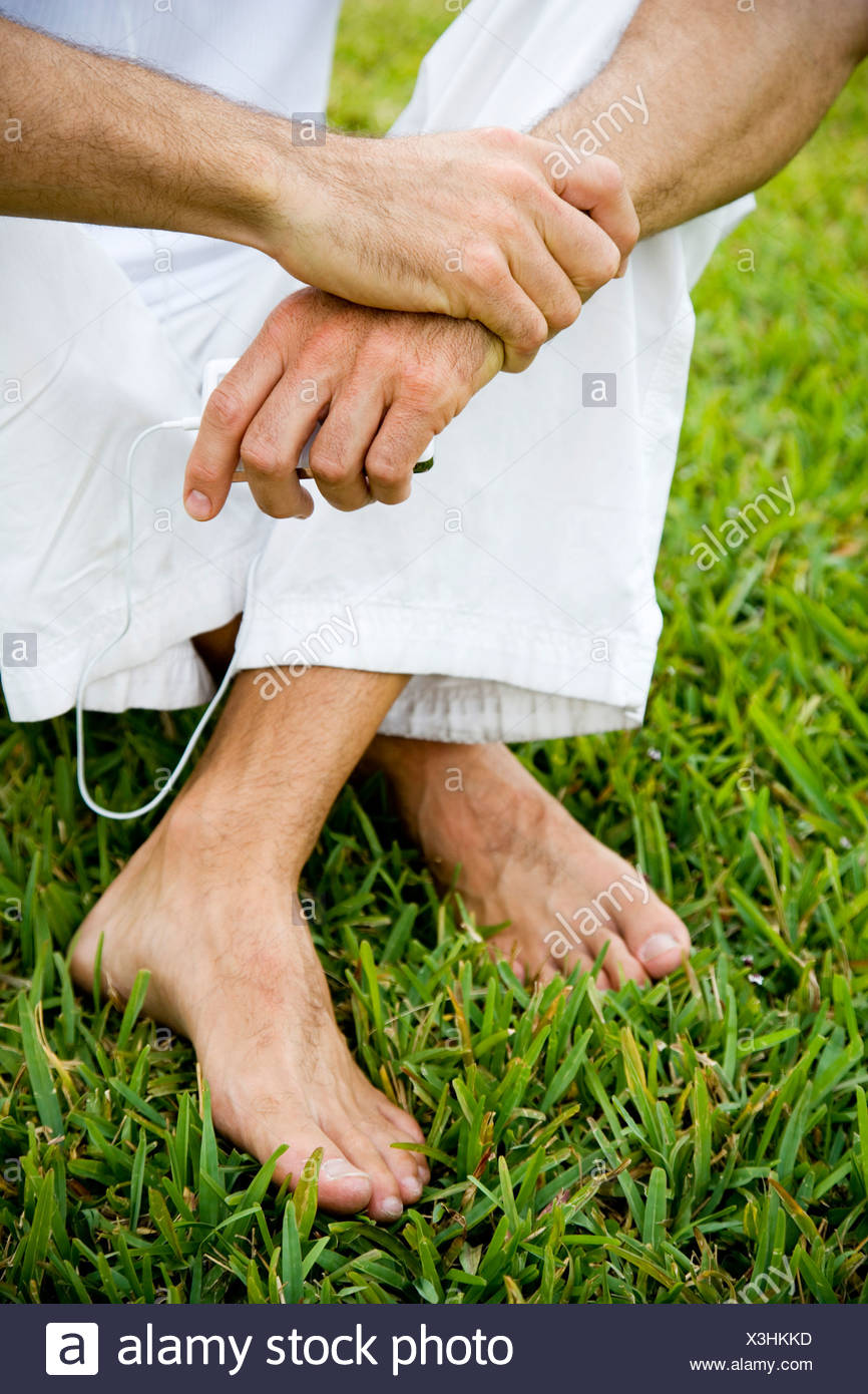 cropped image man's legs and bare feet on grass - Stock Image