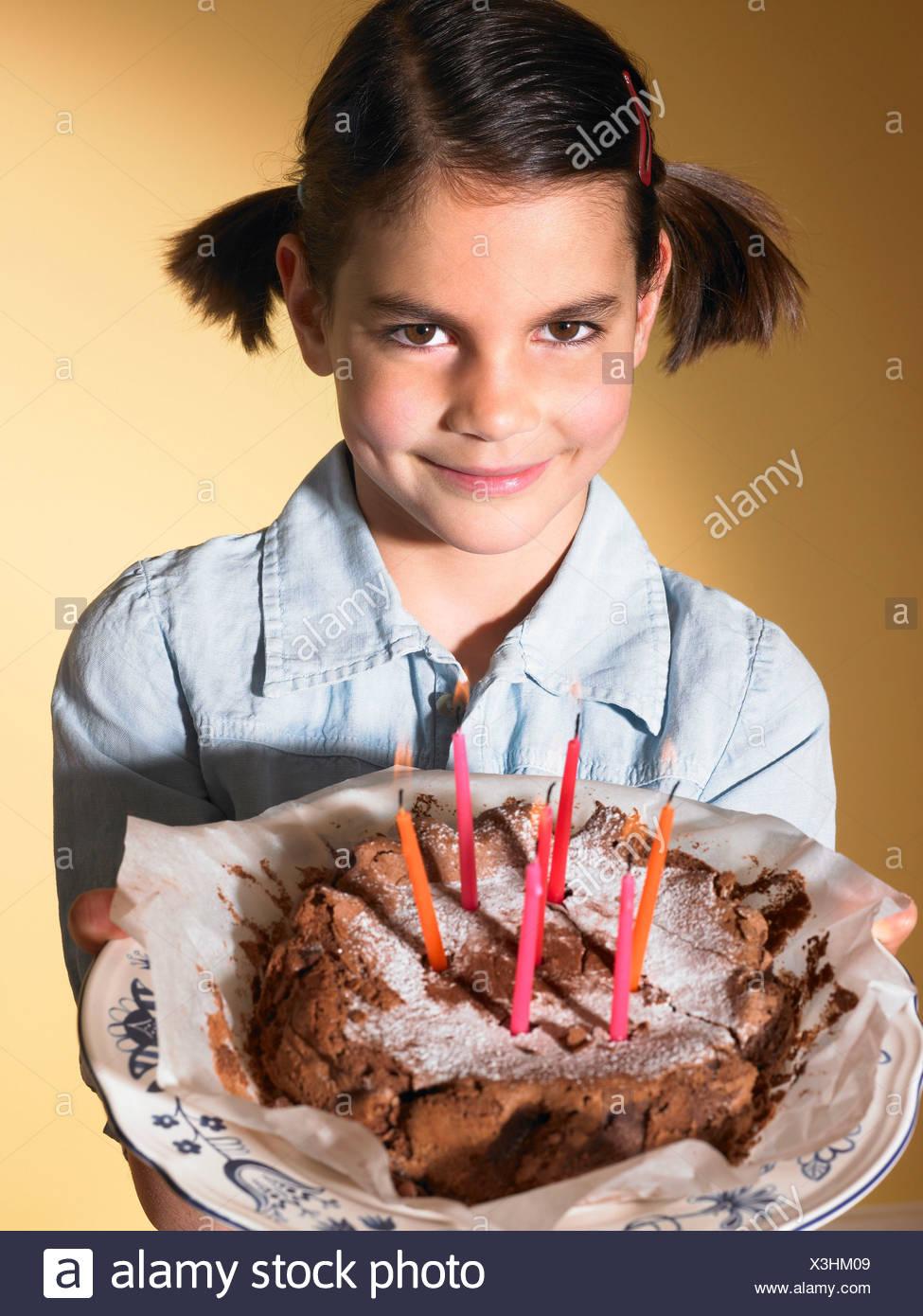 Girl holding a birthday cake - Stock Image