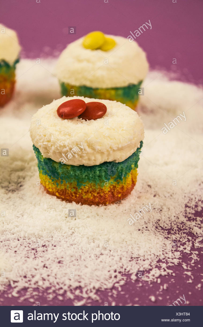 Cupcakes in prismatic colours sprinkled with grated coconut - Stock Image