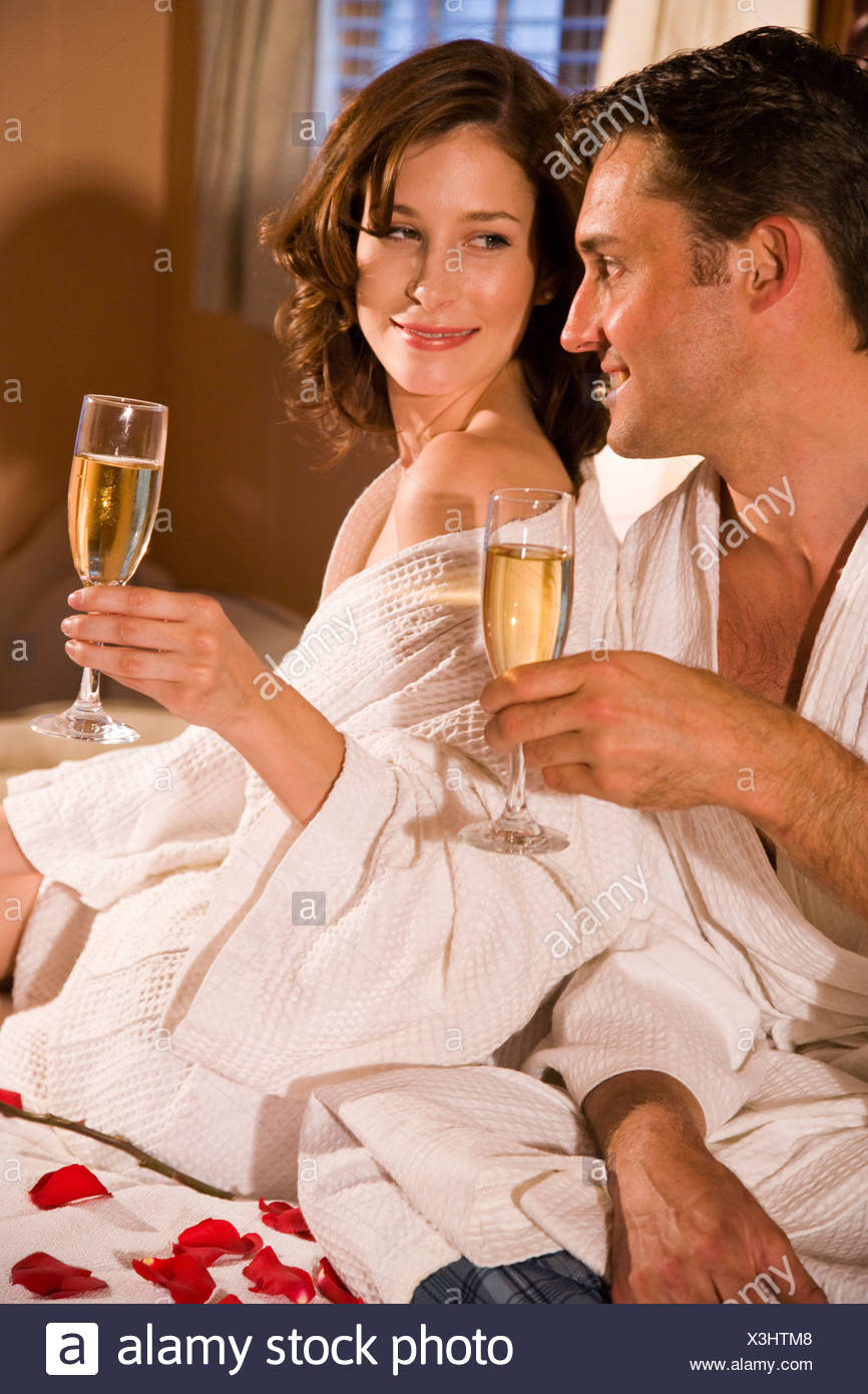 Romantic couple in bathrobes, sitting on bed sipping champagne - Stock Image