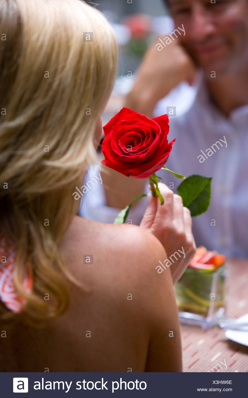 Woman with red rose, rear view - Stock Image
