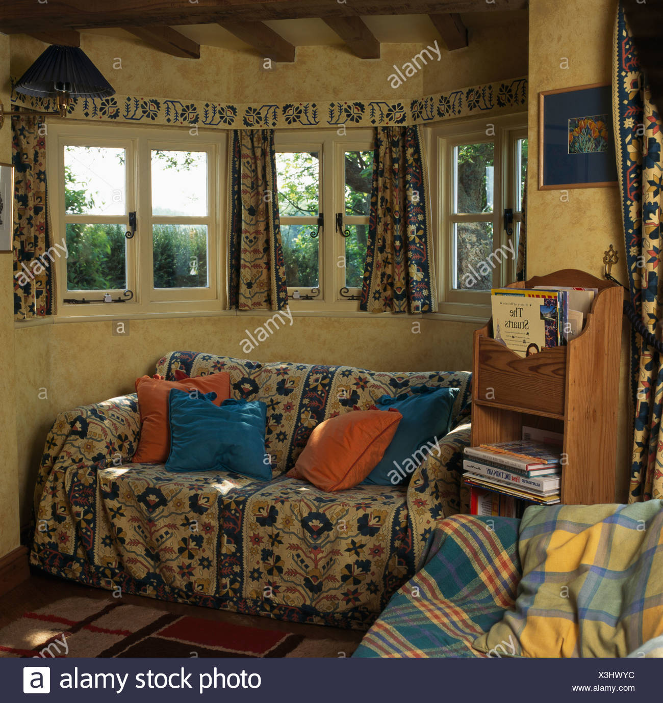 Wallpaper border and small windows above sofa covered with patterned ...