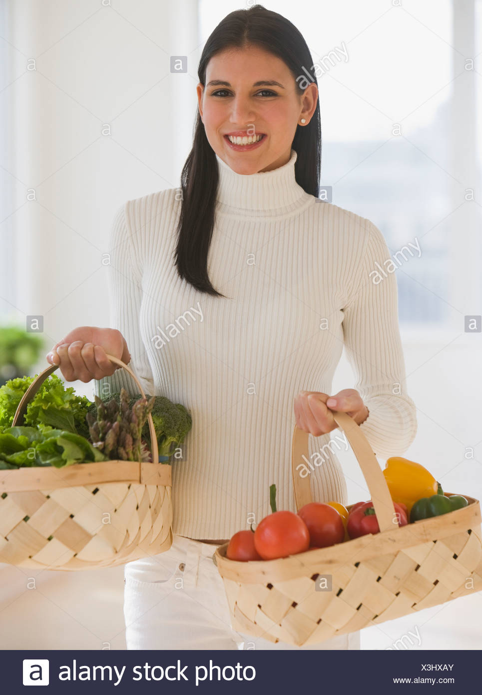Woman carrying baskets of fruit and vegetables - Stock Image