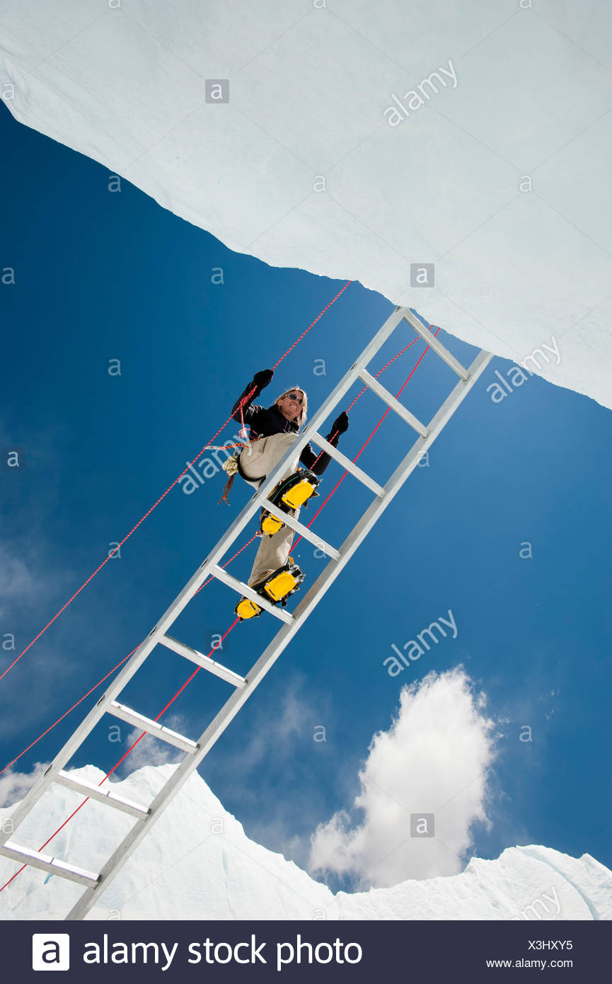 A climber makes her way across a crevasse using a temporary ladder - Stock Image