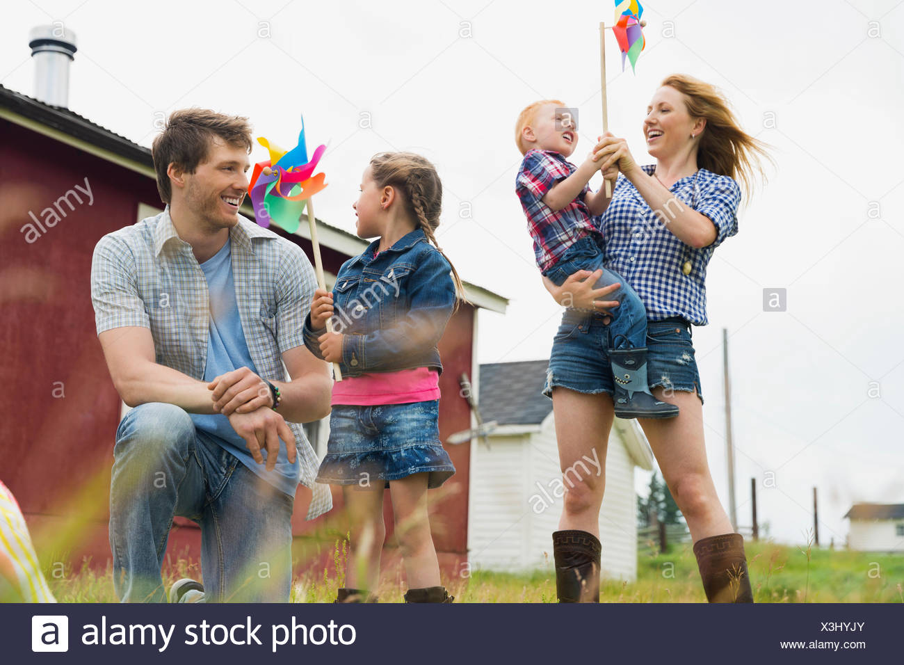 Parents with children holding pinwheels - Stock Image