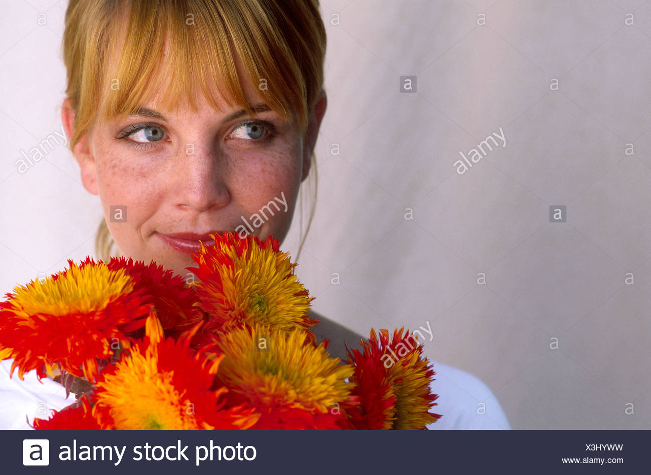 Woman holding up bright bouquet of flowers - Stock Image