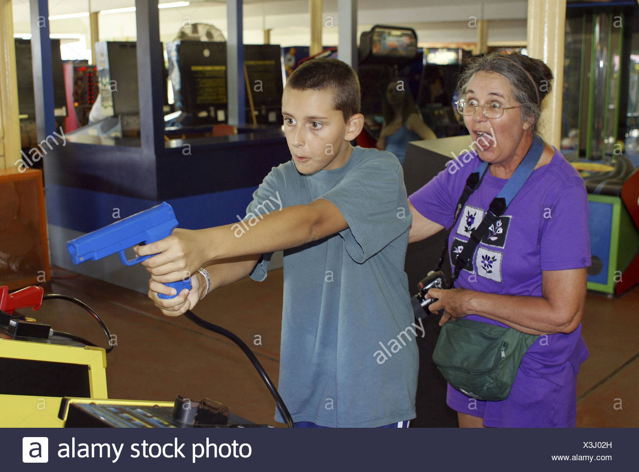 Woman excited by grandson´s accuracy at a game in an arcade. - Stock Image