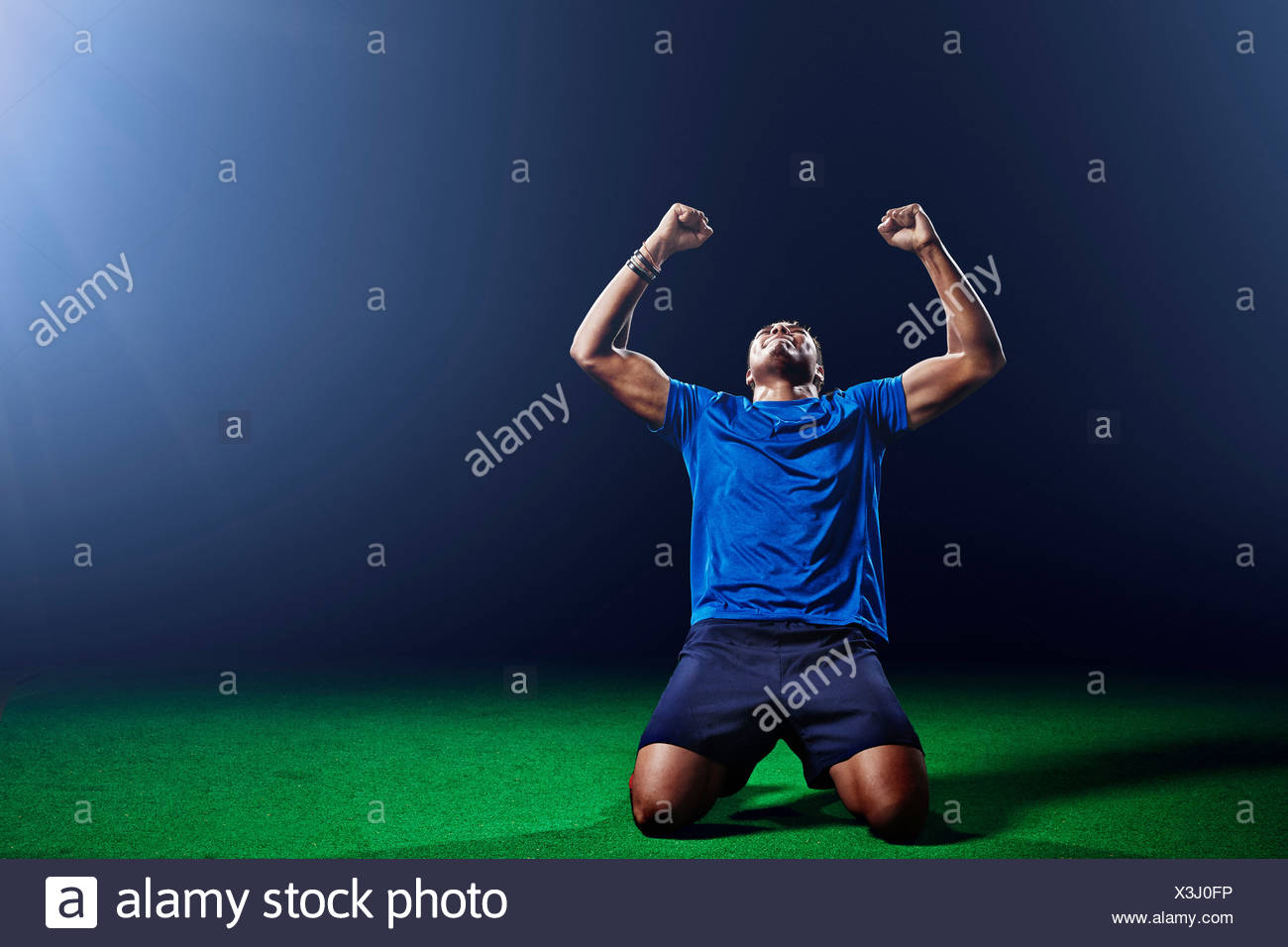 Male soccer player kneeling with arms raised - Stock Image