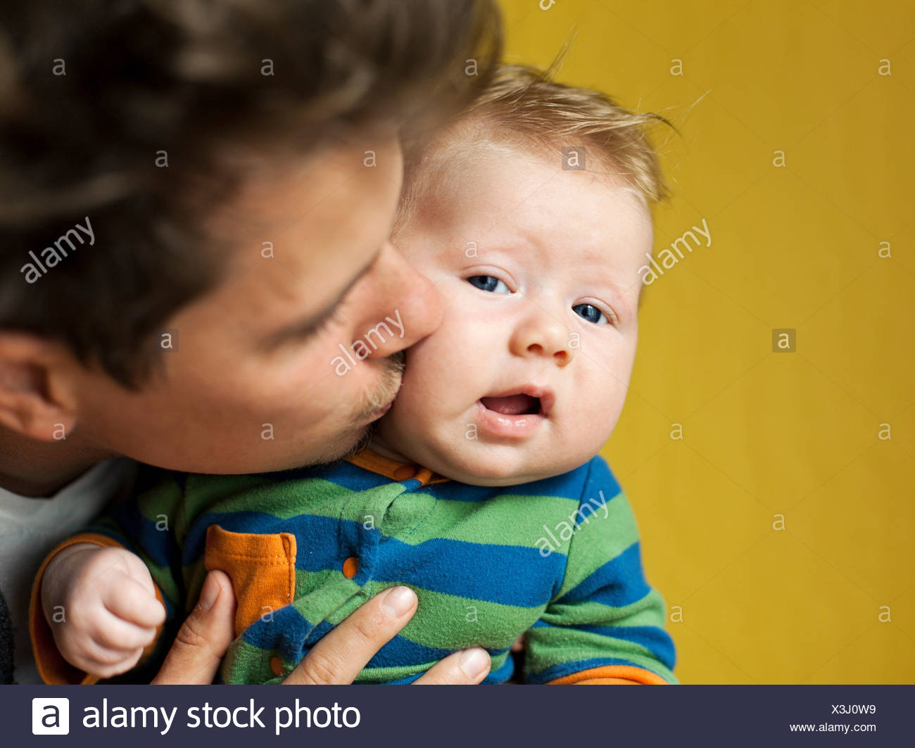 Father kissing baby boy - Stock Image