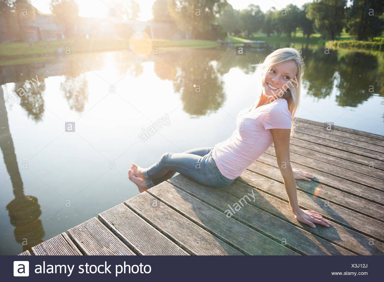 Young woman sitting on pier by lake Stock Photo
