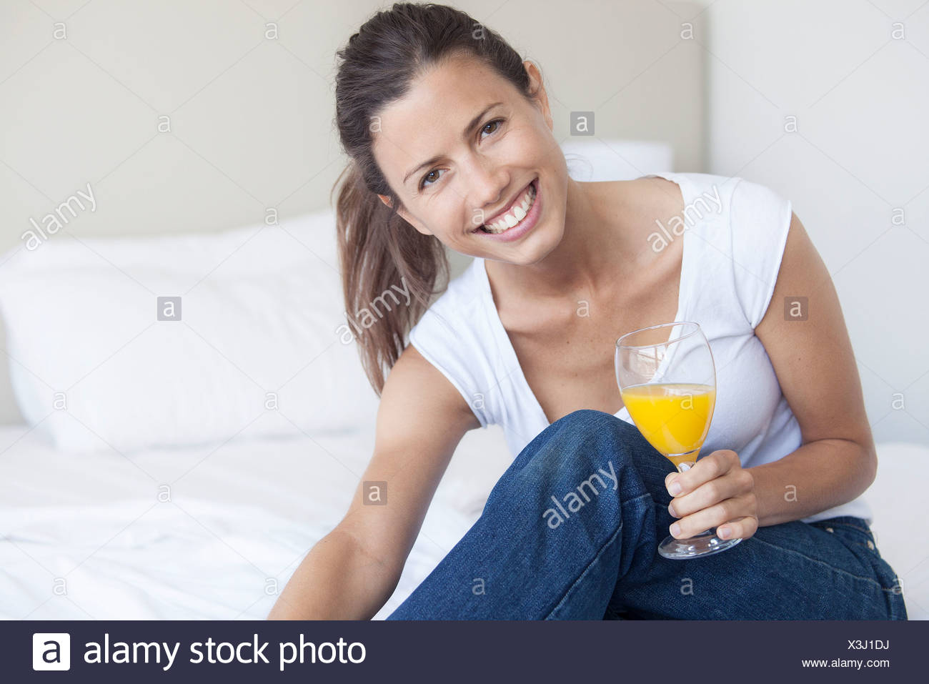 Young woman starting her day with glass of orange juice - Stock Image