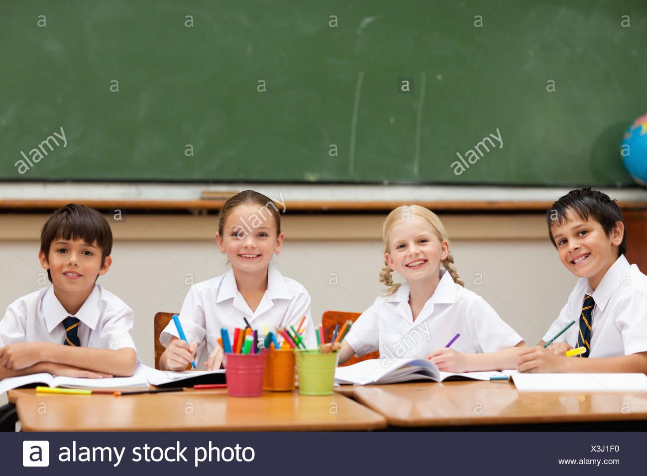 Smiling schoolchildren sitting at desk together Stock Photo