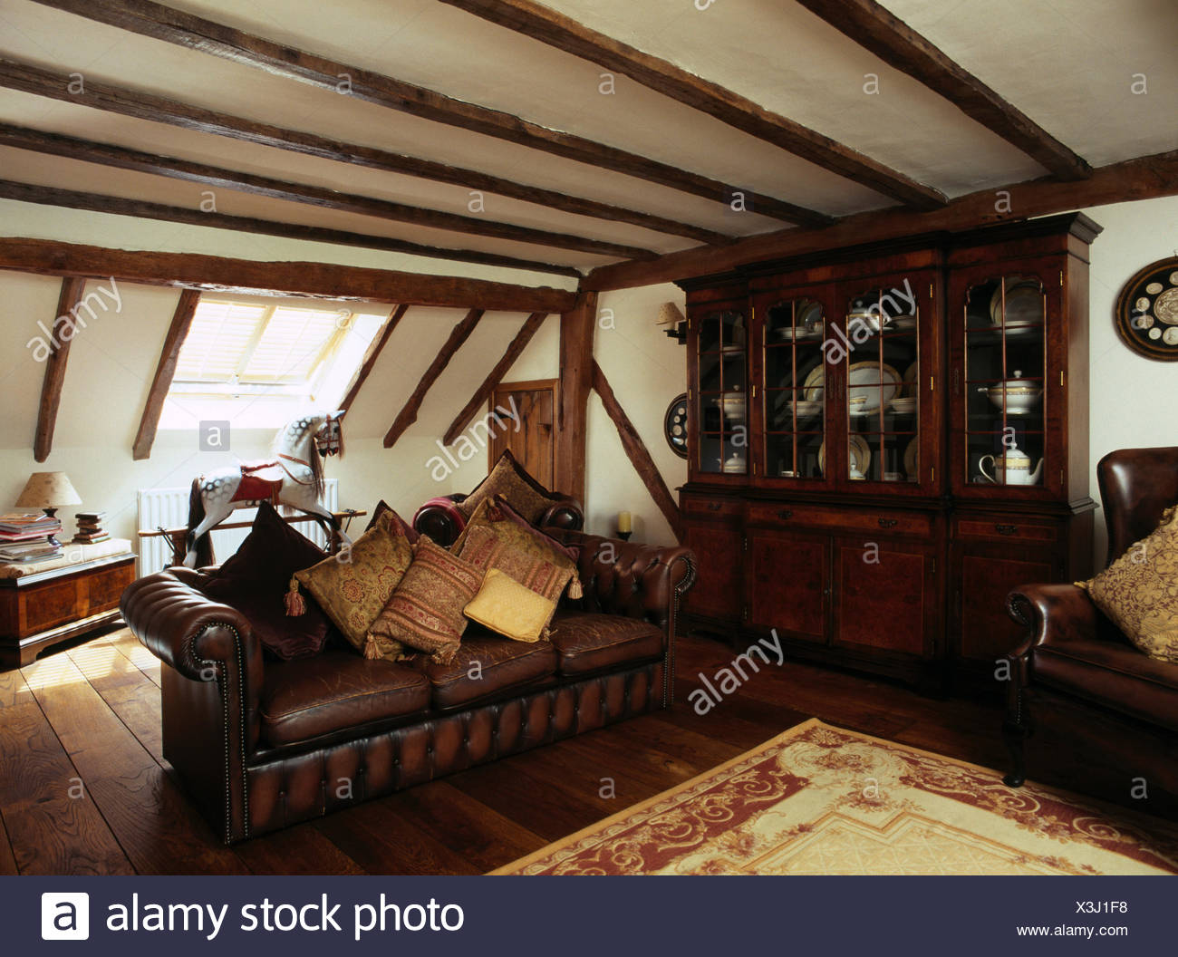 Leather sofa piled with cushions in attic living room with ...