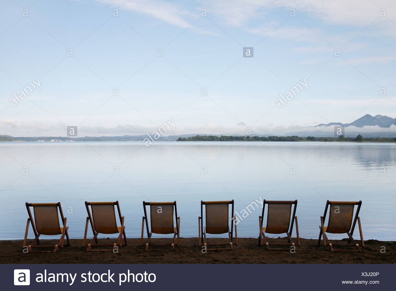 Germany, Bavaria, Chiemsee, Row of folded chairs by lake Stock Photo
