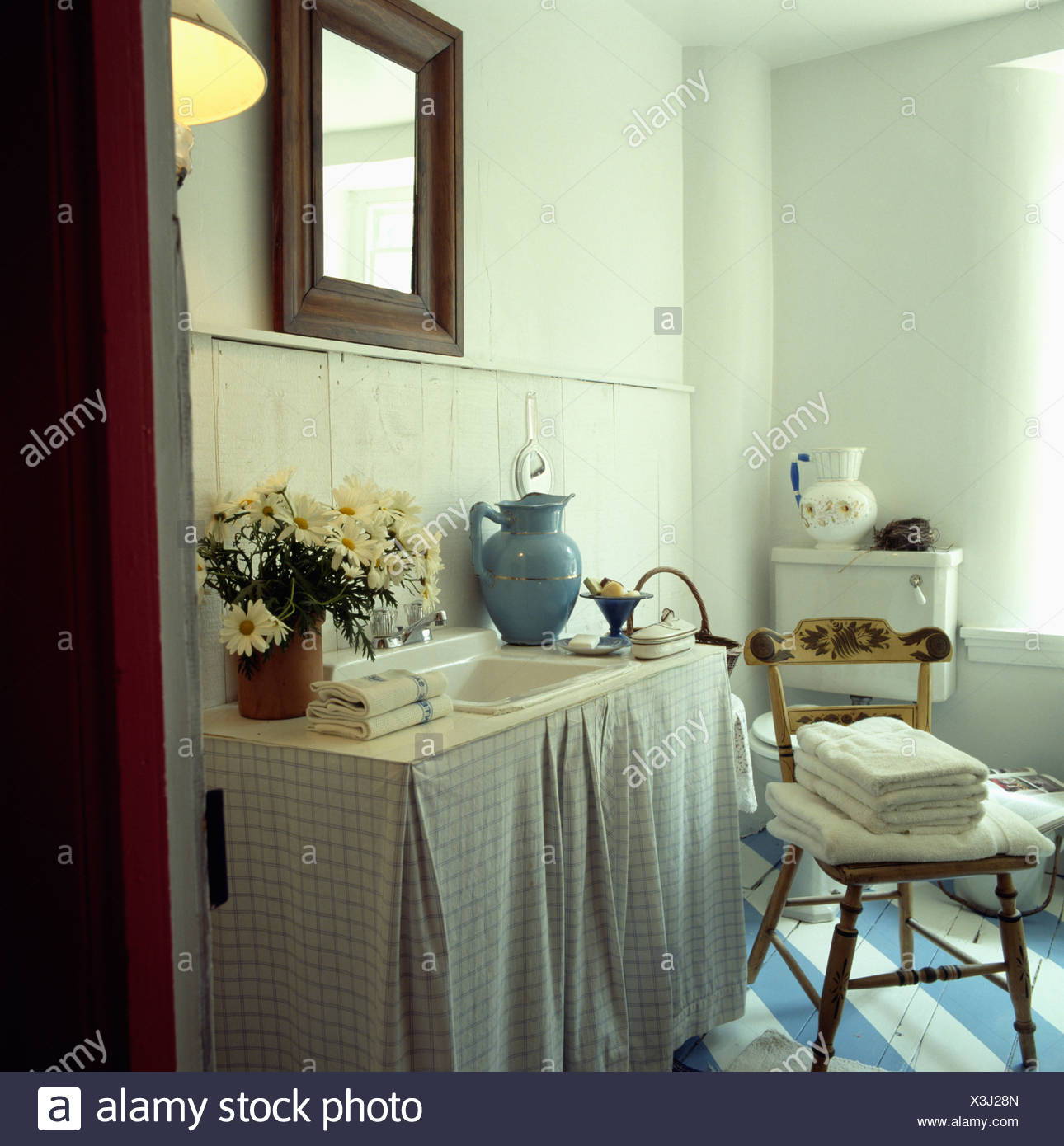 White Towels On Wooden Chair In Country Bathroom With Checked Curtains On Vanity Unit Below Basin Stock Photo Alamy