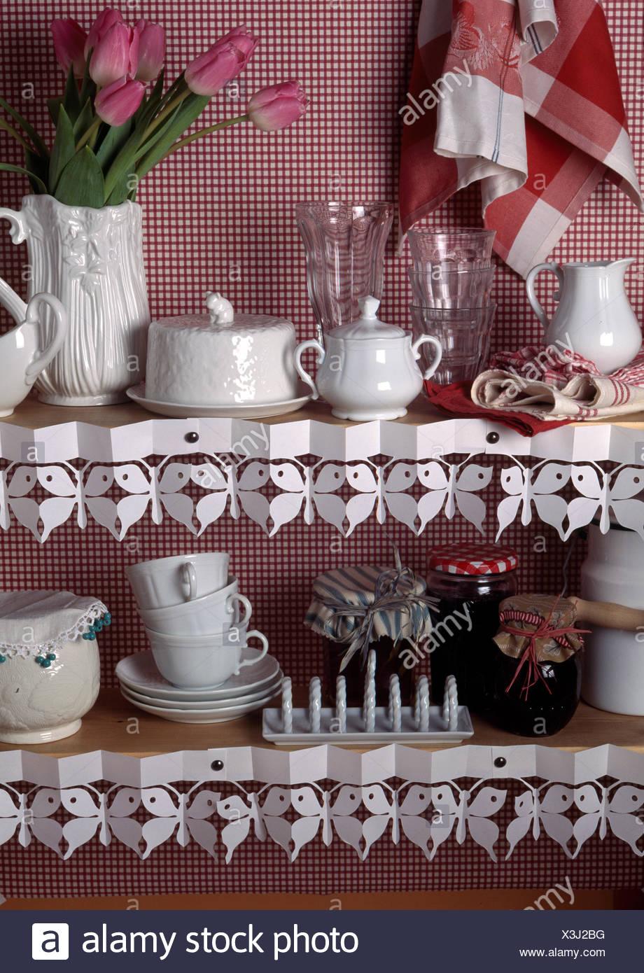 White crockery on kitchen shelves with decorative paper trim ...
